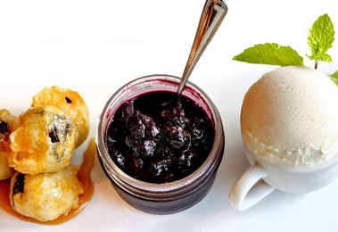 Three desserts - fritters, berry compote and vanilla ice cream - on a clean white plate.