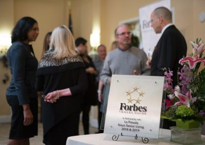 Close up of Forbes Travel Guide partnership plaque on table at event with people out of focus in background.