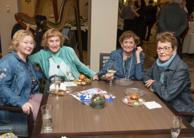 Four women sitting together at a table with drinks and snacks at a resident mixer.