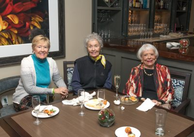 Three women sitting at a table by the bar with drinks and snacks at a resident mixer.