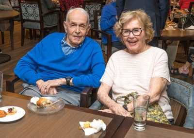 Resident couple enjoying snacks and drinks at a community mixer.